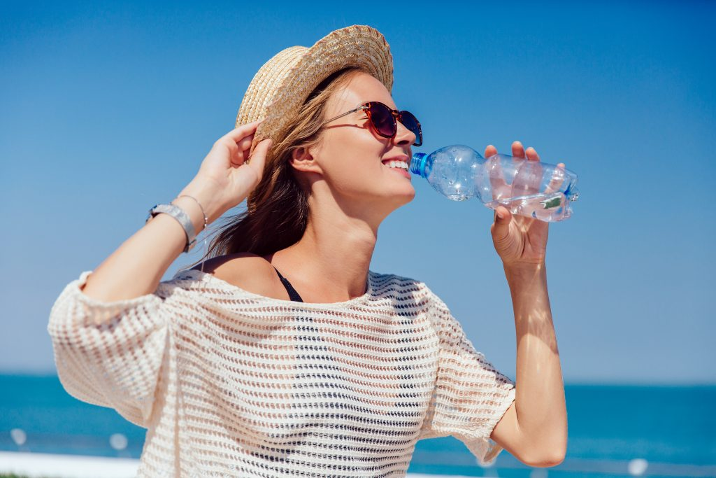 Chica bebiendo agua con sombrero en la playa